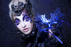 Creative lady. Dark queen. Young woman in creative halloween image posing with mask Stock Photo