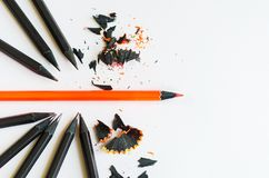 Creative layout of black and one red pencil on white background. `Be different` concept Stock Image