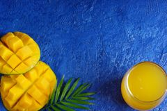 Creative layout on a blue background with mango, a glass of juice and a palm leaf. royalty free stock image