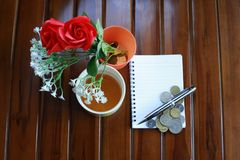 Note book, pen, coins, cup of hot tea and red roses decoration isolated on wooden background. Stock Photos