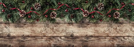 Creative layout frame made of Christmas fir branches, pine cones and red decoration on wooden background. Xmas and New Year theme. stock images