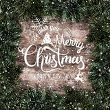 Creative layout frame made of Christmas fir branches with snowflakes on wooden background. Merry Christmas and New Year. Typographical on Xmas card. Flat lay royalty free illustration