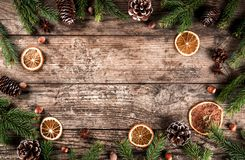 Creative layout frame made of Christmas fir branches, spruce, slices of orange, pine cones, snowflakes on wooden background. Xmas and New Year theme. Flat lay royalty free stock photos