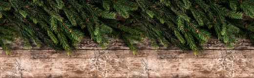 Creative layout frame made of Christmas fir branches on wooden background. royalty free stock image