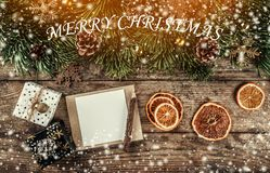 Creative layout frame made of Christmas tree branches, paper card note, pine cones, gifts, gold decoration on wooden background. Xmas and New Year theme royalty free illustration