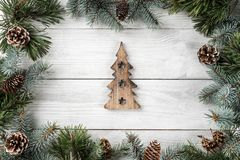 Creative layout frame made of Christmas tree branches and pine cones on white background with figurine of wood Christmas tree. Xmas and New Year theme. Flat royalty free stock photography