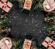 Creative layout frame made of Christmas tree branches, pine cones, gifts on dark background. Xmas and New Year theme, snow. Flat lay, top view, space for text stock images