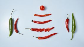 Layout of chili peppers and tomato on gray background stock images