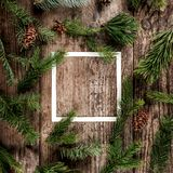 Creative layout made of Christmas fir branches with frame of paper card note, pine cones on wooden background. Xmas and New Year. Theme. Flat lay, top view stock images