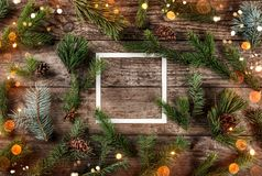 Creative layout made of Christmas fir branches with frame of paper card note and pine cones on wooden background. Xmas and New Year theme, bokeh, sparking royalty free stock photos