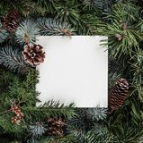 Creative layout made of Christmas tree branches with paper card note, pine cones. Xmas and New Year theme. Flat lay, top view stock photography
