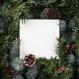 Creative layout made of Christmas tree branches with paper card note, pine cones. Xmas and New Year theme. Flat lay, top view royalty free stock photography