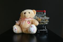 Cute fluffy teddy bear with word love and coins in mini trolley isolated on black dark background. Royalty Free Stock Images