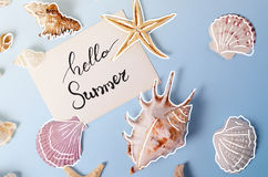 Creative layout made of different colorful seashells and greeting card with Hello Summer Lettering Royalty Free Stock Photography