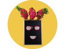 Creative layout made of dragon fruit on the chalkboard frame put a face isolated on yellow circle. On white background. Clipping path stock photo