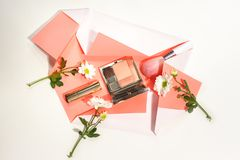 Creative layout made of flowers, blusher palette, powder brush and lipstick on paper of living coral color on white background. stock images
