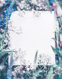 Creative layout made with flowers and leaves around paper card note, blue pastel color. Royalty Free Stock Photography