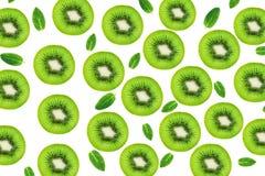 Creative layout made of Kiwi fruits snd mint leaves. Many slices of ripe and juicy Kiwifruit. Flat lay. stock image