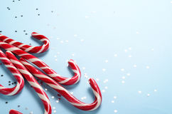 Creative layout made of lollipop cane and sparkling stars. Christmas holiday background, minimal s concept. Royalty Free Stock Image