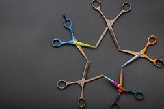 Creative layout made of professional hairdresser scissors in shape of a star on grey-black background. Flat lay