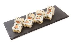 Creative layout made of sushi. Flat lay. Food concept. Macro concept. Sushi isolated on shale food board on white background stock photos