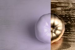 Creative layout made of tomato on wood backgruond. Painted purple and gold. Food concept. Royalty Free Stock Photo