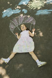 Creative leisure for children. Happy expressive little girl laying down on asphalt dreaming of jumping with parachute, sidewalk drawned with chalk Royalty Free Stock Photo
