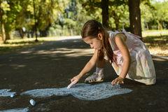 Creative leisure for children. Little girl drawing on asphalt with chalk. Concept of child imagination Royalty Free Stock Photo