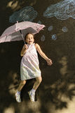 Creative leisure for children. Little girl laying down on asphalt with umbrella after drawing clouds with rain drops with chalk. Concept of child imagination Stock Images