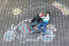 Creative leisure for children: two little funny friends in helmet having fun with motorcycle picture drawing with. Colorful chalks. Children, lifestyle, fun stock photo