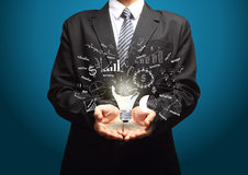 Creative light bulb with drawing business plan in hand Stock Image