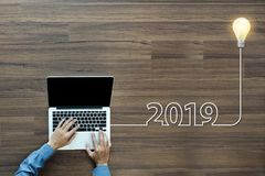 Creative light bulb idea 2019 new year. With businessman working on laptop computer PC, Top view from above royalty free stock photos