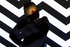 Creative light pattern on posing cool woman with sun glasses Royalty Free Stock Image