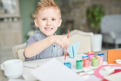 Creative Little Boy at Art Class. Waist-up portrait of cheerful little boy looking at camera with toothy smile while wrapped up in drawing picture at art class royalty free stock photography