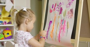 Creative little girl painting an abstract picture stock video footage