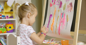 Creative little girl painting an abstract picture Stock Photography