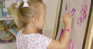 Creative little girl painting in a playroom stock footage