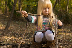Creative little girl playing with wooden twigs Stock Images