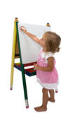 Creative little girl staring to draw on an easel Stock Images
