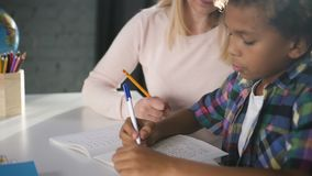 Creative long hair mother is candid looking and helping son. In writing elementary school exercises. Smart hispanic preteen is sitting at the table and getting stock footage