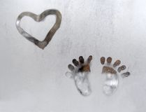 Creative love drawing on a frozen window. Creative frozen window drawing looking like a child drawing, heart and footsteps, on white background Royalty Free Stock Image