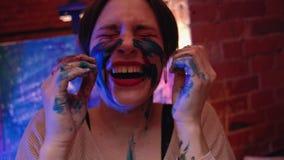 Creative madness joyful woman face paint laughing