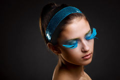 Creative make-up. The head of a girl with creative make-up and eyes closed on a dark background royalty free stock image