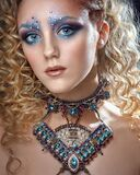 Creative make-up in shades of blue with rhinestones.