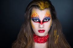 Flame art make up. Creative makeup, crazy conceptual idea for Halloween. red blue golden bold body art painting. Crazy new graphic abstract picture on woman face Royalty Free Stock Images