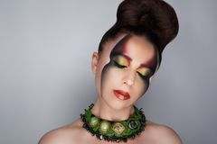 Woman art make up. Creative makeup, new crazy conceptual idea for Halloween. black green red bold body art painting. graphic abstract picture on woman face Royalty Free Stock Image