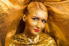 Golden make up. Creative makeup, new crazy conceptual idea for Halloween. golden red bold body art painting. Crazy new graphic abstract picture on woman face Royalty Free Stock Image