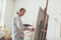 Creative male artist drawing picture oil paints Stock Image