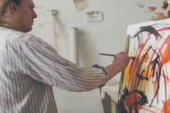 Creative male artist drawing picture oil paints Stock Photo