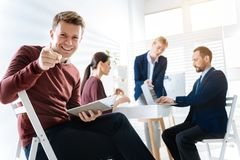 Creative male colleague laughing at joke. Funny joke. Cheerful handsome male colleague pointing at the camera while carrying notebook and laughing Stock Images